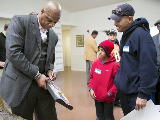 Retired baseball player Darryl Strawberry, left, signs autographs for Angel Alvarez, center, and his father Gilbert Alvarez at the 2014 opening of the Darryl Strawberry Recovery Center in St. Cloud, Fla. Strawberry has become an ordained minister and will speak to the crowd at Santander Stadium before the York Revolution's game on Saturday, June 27, for Faith and Family Night.