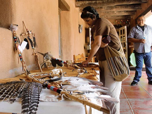 A visitor of White Sands browses Sam Gutierrez's work on Saturday afternoon during the Native American Artist Craft Show and Demonstration. Gutierrez is part of the Ysleta del Sur Pueblo, which is 12 miles from downtown El Paso.