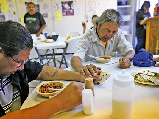 Nelson Simpson, left, and Chris Begay pray Wednesday before dinner at Catholic Charities in Farmington.