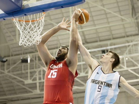 Team Canada's center and former New Mexico State player Sim Bhullar, left, battles for a rebound with Argentina's Nicolas Brussino during the men's basketball tournament at the Pan Am Games in Toronto on Wednesday.