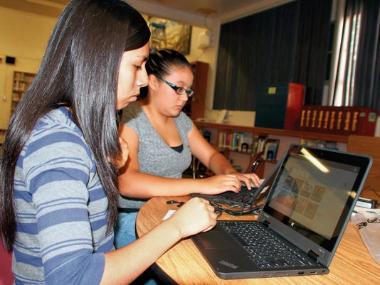 """Bill Armendatriz — Headlight Photo   Freshmen Brianna Almanza, 13, and Diana Orozco, 14, spent Tuesday morning personalizing and setting up their new Lenovo 2-in-1 notebook computers. Every registered Deming High School student is receiving a computer. They school staff will complete the distribution process after today at the high school. """"This is cool, because I never had my own laptop. It will inspire me to study more,"""" Orozco said. Almanza added, """"It will help me do better with my education."""""""