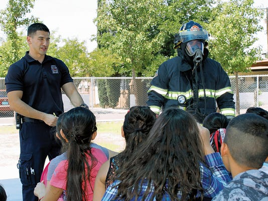 Bill Armendariz - Headlight Photo   Deming Firefighters/EMTs Jordan Ramirez, left and Fernie Aernibas talk to students abour fire safety and demonstrate the use of firefighting gear.