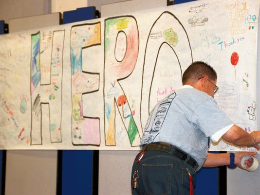 """By Bill Armendariz — Headlight Photo   Danny Rodriguez helped decorate the Memorial Elementary School Gymnasium during last Friday's Heroes' Appreciation Day in conjunction with the 9/11 memorial. Rodriguez teaches at the school and has spent most of his adult life in education for the Deming Public Schools. He has also had a long career in sports broadcasting as the """"Voice of the Deming Wildcats for local radio station KOTS-1230AM/KDEM-94.3FM."""