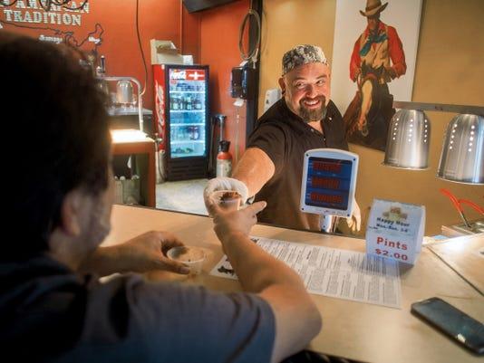 Jett Loe--Sun-News   Mesilla Valley BBQ Co. cook Steve Marquez hands a sample to take-out customer Steve Stevens.
