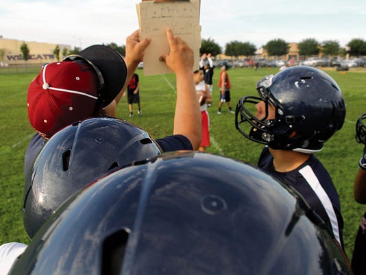 Deming High offensive coordinator Richard Perales goes over a play with the Wildcat offensive unit during Monday's morning practice session. Two-a-day workouts began on Monday and will continue thorugh the week.