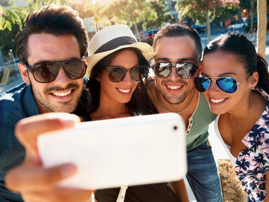 ThinkStockImages.comPortrait of group friends taking photos with a smartphone.