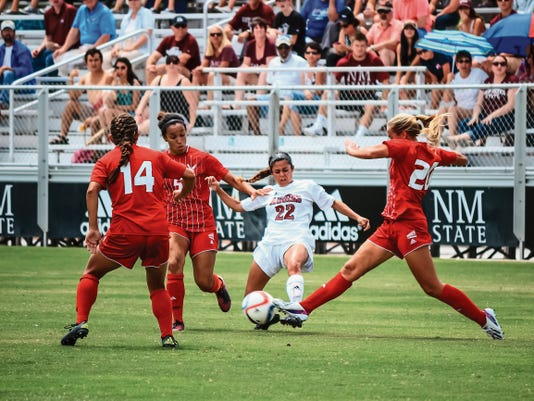 Jermey Perlman -- For the Sun-News   New Mexico State's Gabby Campbell (22) tries to get past Eastern Washington's Devan Talley (14), M'Kenna Hayes (5) and Kiana Hafferty, right, during the Aggies' season opener Sunday afternoon at the NMSU Soccer Athletic Complex.