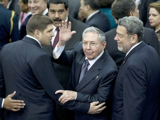 Cuba's President Raul Castro, center, waves at photographers Saturday as he leaves accompanied by Prime Minister of Saint Vincent and the Grenadines Ralph Gonsalves, right, and an unidentified Cuban official at the end of the VII Summit of the Americas' official group photo, in Panama City.