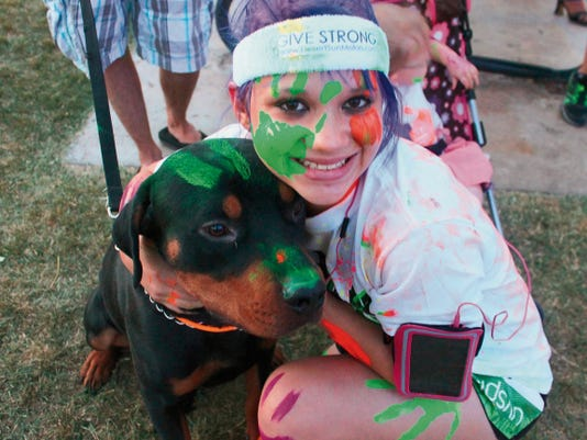 Kaiya Buchholz and her dog, Bubba get painted before the UV Splash 5K started at dusk. The UV water sprayed on participants at the completion of each mile was a non-toxic mixture of UV dye and water.