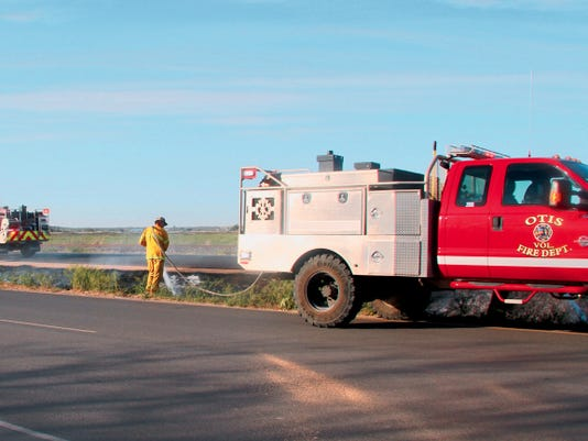 SARAH MATOTT - CURRENT-ARGUS   Firefighters from the Otis Volunteer Fire Deparment extinguish what was left of a grassfire that broke out on the on south U.S. 285 toward Loving. The grassfire occured in the medium and caused traffic heading to Carlsbad to be temporarily stopped.