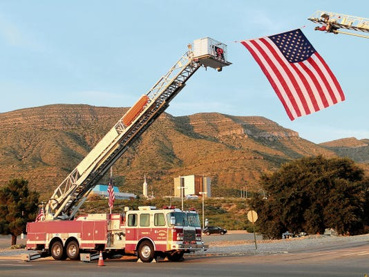 An American flag hangs from two fire trucks at the New Mexico Museum of Space History during the Otero County Firefighters Association's annual Sept. 11 Memorial Ceremony.