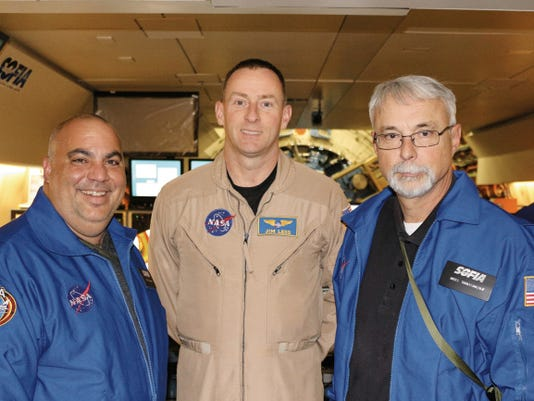 """Jim """"Clue"""" Less (center), a former F-117A Nighthawk stealth fighter pilot at Holloman Air Force Base, flew the SOFIA 747 the week of September 14. On board were Jeff Killebrew (left), science teacher at the New Mexico School for the Blind and Visually Impaired, and Michael Shinabery (right), of the New Mexico Museum of Space History. SOFIA, or the Stratospheric Observatory For Infrared Astronomy, is based in Palmdale, California. Less is now a NASA test pilot. This photo was taken in the wee hours of Sept. 18, at 43,000 feet altitude."""