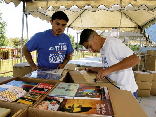 Volunteers Lenart Tso and Marcos Candelaria open boxes in September 2014 in preparation for the Farmington Public Library's annual book sale. This year's event opens its five-day run on Saturday, Sept. 12.