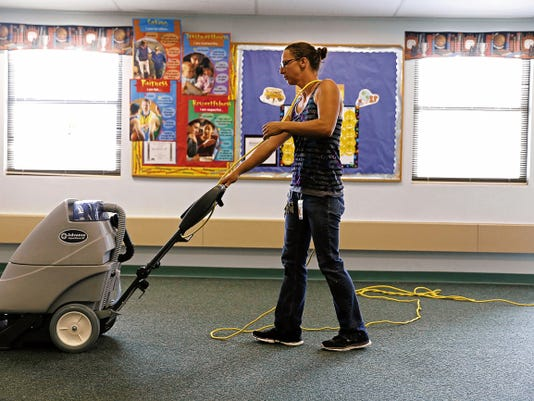 Mandy Livingston, custodial maintenance worker, vacuums up water in a classroom after flooding on Aug. 27 at Lydia Rippey Elementary School in Aztec.