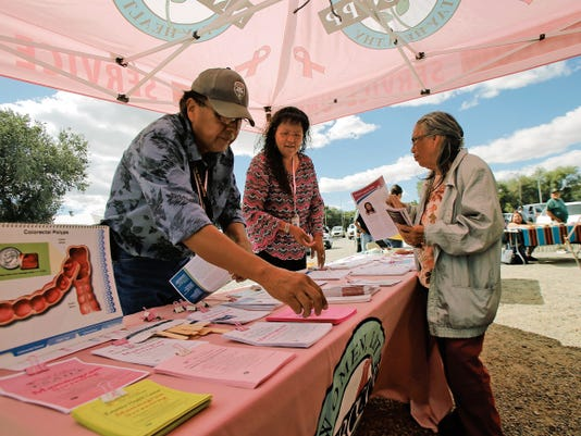 Navajo Nation Breast and Cervical Cancer Prevention Program health educator Jonah H. Yazzie, left, and case manager Rosilyn Smith hand out information on Wednesday during the Stop Elder Abuse Awareness Day event at the Shiprock Chapter house.