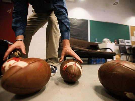Shiprock football head coach Eric Stovall shows vandalized footballs Wednesday at Shiprock High School.