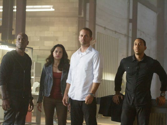 "This photo provided by Universal Pictures shows, from left, Tyrese Gibson as Roman, Michelle Rodriguez as Letty, Paul Walker as Brian, and Chris Ludacris as Tej, in a scene from ""Furious 7."""