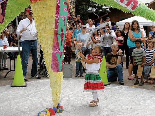 Isabella Alirez, 4, takes a swing at the 16-foot piñata during Sacred Heart Feast Day Celebration in Cloudcroft Saturday. Isabella was one of hundreds of children who got a chance to release 50 pounds of candy during the fiesta. The piñata had seven symbolic rays of the seven deadly sins and kids struck it with wooden weapons painted to represent each of the seven virtues.