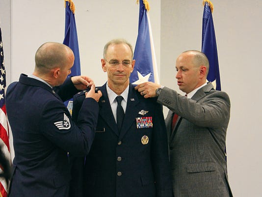 Staff Sergeant Ross Ediger, left, and Zachery Ediger, pin the third star on their father, Lt. Gen. Mark Ediger during the promotion ceremony June 8 at the Defense Health Headquarters, Falls Church, Virginia. General Ediger became the 22nd Air Force Surgeon General during the ceremony, officiated by Vice Chief of Staff Gen. Larry O. Spencer.