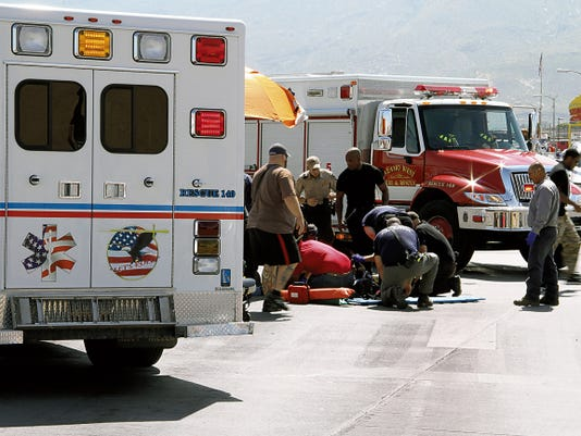 American Medical Response and Alamo West paramedics treat one of the injured motorcyclist at 10th Street and Florida Avenue Saturday during Alamogordo's July Fourth parade. Two motorcyclists who were participating in the Alamogordo crashed into each other causing the parade to be delayed for between 20 and 30 minutes.