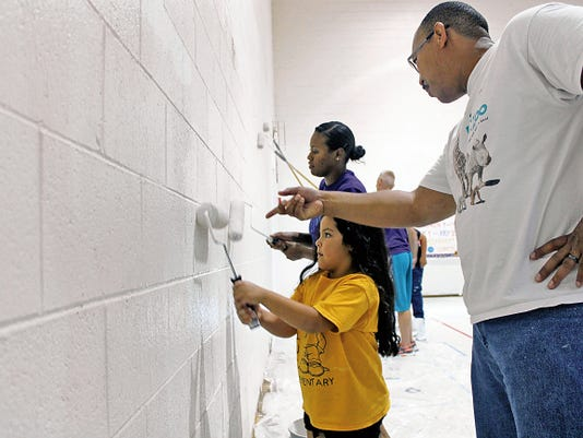 Liliana Amaya, 6, learns how to paint from her new principal Richard Harrid during Holloman's Big Give project on Saturday. The Mighty Murphs, of Holloman, gave the La Luz Elementary dual purpose cafeteria a much needed painting as part of one of their two community projects.