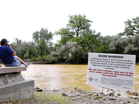 A river warning sign from the city is placed in front of the Animas River as orange sludge flows, Saturday, Aug. 8, 2015, at Berg Park in Farmington.