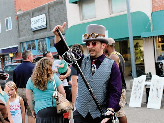 Mike Elliott entertains the crowd during the Art Walk on Friday evening.