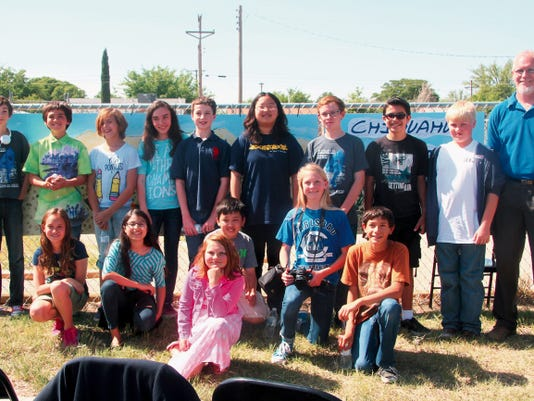 SARAH MATOTT - CURRENT-ARGUS   Damian Armijo, project facilitator, and students who helped construct the school-yard habitat at the Alta Vista Campus pose in front of the trail's entrance.
