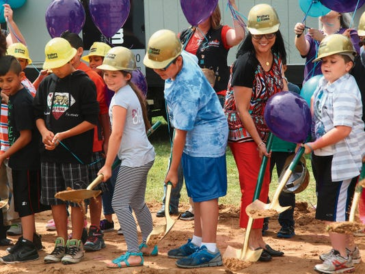 KATIE ENGLAND -- CURRENT ARGUS   Third graders from Pate Elementary School help Principal Nora Villareal move dirt as part of the groundbreaking ceremony for the Desert Willow Elementary school on Wednesday. These students will be the first class to graduate from the new building.