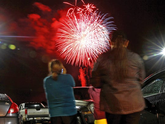 Spectators watch the city's official fireworks show from the parking lot at San Juan College in Farmington in this file photo.
