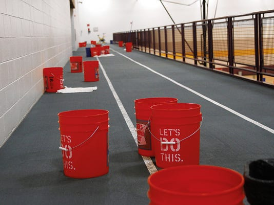 Buckets on June 17 line the running track at the gym inside the Health and Human Performance Center at San Juan College in Farmington after hail damaged the roof.