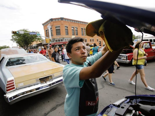Samuel Ortiz cleans his uncle's 2003 Ford Mustang Saturday during the annual Rod Run Show N' Shine Block Party in downtown Farmington.