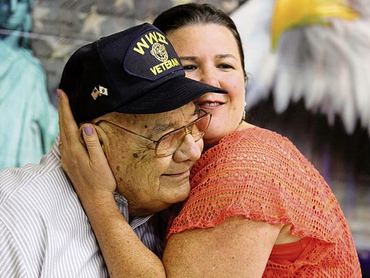 World War II veteran Leroy Bussell receives a hug from his granddaughter Suzanne Buemi, of Denver, after he was presented his Purple Heart Saturday during a ceremony at VFW Post 614 in Aztec.