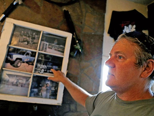 Owner Vince Blume shows old photos of the business Friday at The Paint Zone in Farmington.