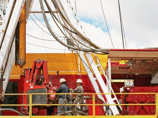 "Rig workers work April 28 on a well at WPX Energy's ""Aztec 1000"" walking rig in Lybrook."