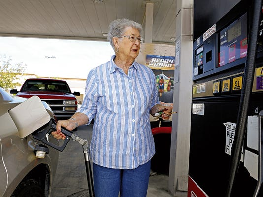 Louise Estep, of Farminton, pumps gas on Tuesday at the gas station at Smith's Food and Drug in Farmington.