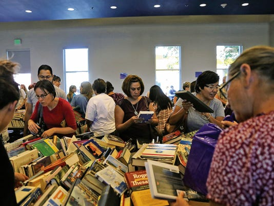 Shoppers browse through stacks of books Saturday during the Farmington Public Library's annual book sale.