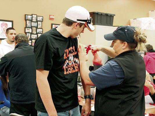 San Juan County Fire Division Chief Laura Hensley applies moulage makeup to a volunteer participant in preparation for the San Juan County emergency drill on Oct. 12, 2013, at the college in Farmington.