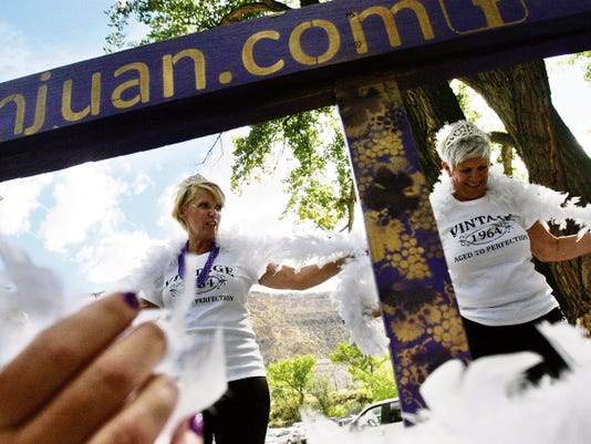 Kimber Bruce, left, and Kate Zemke shake their boas before competing against each other in the Great Grape Stomp during the 2014 Harvest Wine Festival at Wines of the San Juan in Blanco.
