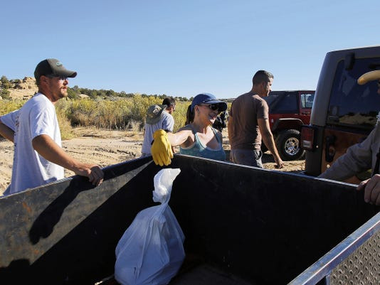 Local volunteers and members of Farmington's CliffHangers Four Wheel Drive Club remove trash Saturday during National Public Lands Day in the Glade Run Recreation Area in Farmington.