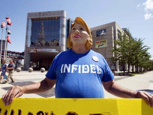 Bob Kunst of Miami Beach, Fla. wears a Hillary Rodham Clinton mask and holds an anti-Hillary poster outside the Quicken Loans Arena in Cleveland, Wednesday, Aug. 5, 2015, before Thursday's first Republican presidential debate being held at the arena. (AP Photo/Andrew Harnik)