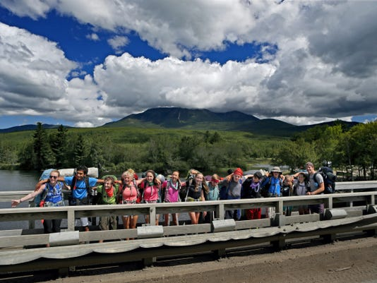 In this Friday, Aug. 7, 2015 photo, a group of section-hikers pose for a photo on a logging road outside Baxter State Park before continuing on the Appalachian Trail to Mt. Katahdin, in background. The sharp rise in the number people using the Appalachian Trail is causing headaches for officials, who say they're dealing with more problems along the more than 2,000-mile footpath than ever.   (AP Photo/Robert F. Bukaty)