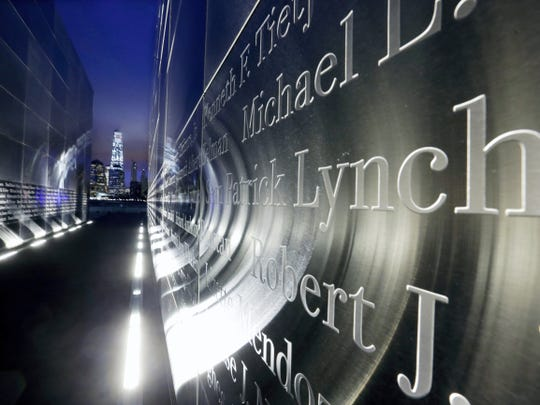 """The names are seen on the """"Empty Sky"""" memorial to New Jersey's victims of the Sept. 11, 2001 terrorist attacks, as One World Trade Center, center left, stands on the 14th anniversary, early Friday, Sept. 11, 2015, in Jersey City, N.J.  Victims' relatives began marking the 14th anniversary of Sept. 11 in a subdued gathering Friday at ground zero, with a moment of silence and somber reading of names. (AP Photo/Mel Evans)"""