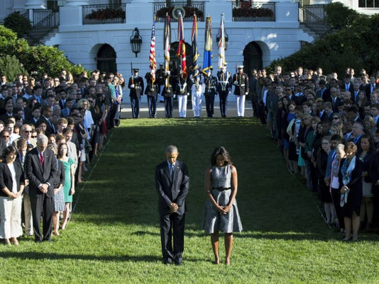 President Barack Obama, first lady Michelle Obama, and others, stand on the South Lawn of the White House in Washington, Friday, Sept. 11, 2015, as they observe the 14th anniversary of the 9/11 terrorists attacks. (AP Photo/Evan Vucci)