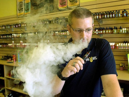 """SS Vape district manager Jason Goin vapes in the store at Manchester Crossroads shopping center Thursday, July 2, 2015. He says vaping helps people quit smoking, which he did 3 1/2 years ago by vaping. The store initials stand for """"stop smoking."""""""