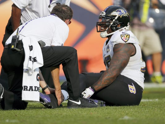 Baltimore Ravens outside linebacker Terrell Suggs is treated on the field during the second half against the Denver Broncos on Sunday in Denver. Suggs suffered a torn left Achilles tendon and will miss the rest of the season.