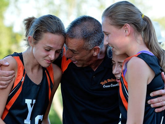York Suburban coach Dan Vanhouwe congratulates Cecilia Lantz, left, Zette Pflaum, and Brooke Ruth after the girls' team won a cross country meet at Codorus State Park on Tuesday.