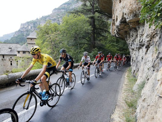 Britain's Chris Froome, wearing the overall leader's yellow jersey, rides in the pack as they pass through Tarn river canyon during the fourteenth stage of the Tour de France on Saturday.