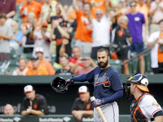Atlanta Braves' Nick Markakis, second from right, removes his helmet as he acknowledges fans in front of Baltimore Orioles catcher Matt Wieters before his at-bat during the first inning of Monday's game. Markakis played his entire major league career with the Orioles before signing during the offseason with the Braves, who were in town Monday for the start of a three-game series.