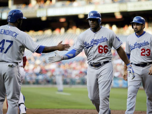 The Dodgers' Yasiel Puig (66), Howie Kendrick (47) and Adrian Gonzalez (23) celebrate after Puig's three-run home run during the first inning of Wednesday's game against the Phillies in Philadelphia. Los Angeles won, 4-3.